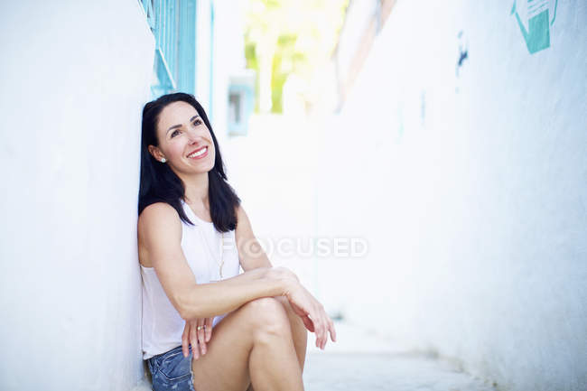 Portrait of smiling, confident woman relaxing in summer alley — Stock Photo