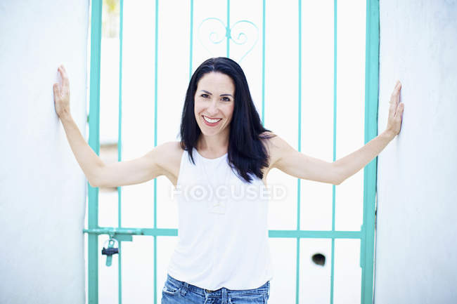Portrait of confident, smiling woman standing in front of turquoise summer gate — Stock Photo