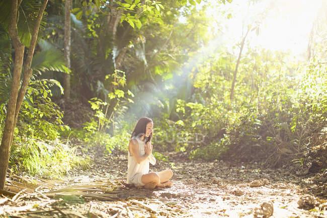 Woman meditating in sunny, tranquil woods, Sayulita, Nayarit, Mexico — стокове фото