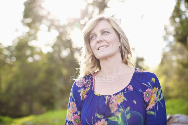 Портрет улыбающейся женщины в солнечном парке — стоковое фото