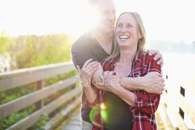 Портрет счастливой, влюбленной пары, обнимающейся на солнечном летнем пешеходном мосту — стоковое фото