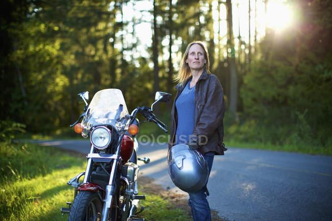 Mujer de confianza en motocicleta en las carreteras de los bosques - foto de stock