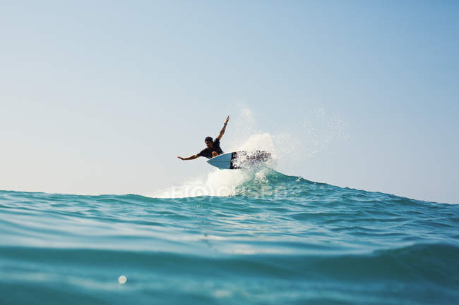 Male surfer riding turquoise blue ocean wave — Stock Photo