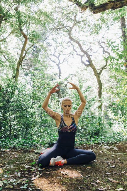 Personal trainer stretching in forest — Stock Photo
