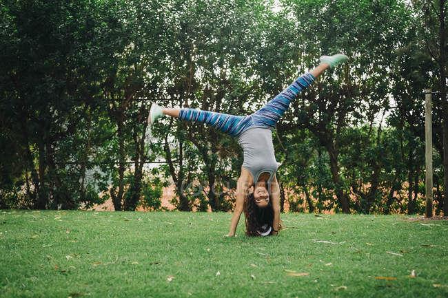 Portrait of carefree female personal trainer doing handstand in park — Stock Photo