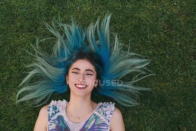 Портрет беззаботной молодой женщины с голубыми волосами, лежащими в траве — стоковое фото