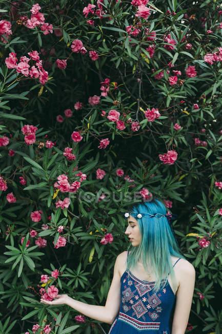 Молода жінка з синім волоссям стоїть під квітковим деревом. — стокове фото