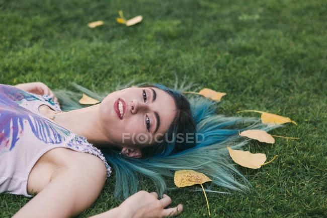 Retrato de mulher com cabelo azul que coloca na grama com folhas de outono — Fotografia de Stock