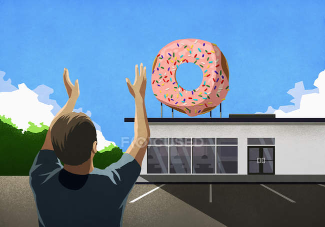 Мужчина с поднятыми руками смотрит на розовый пончик на вершине булочной — стоковое фото