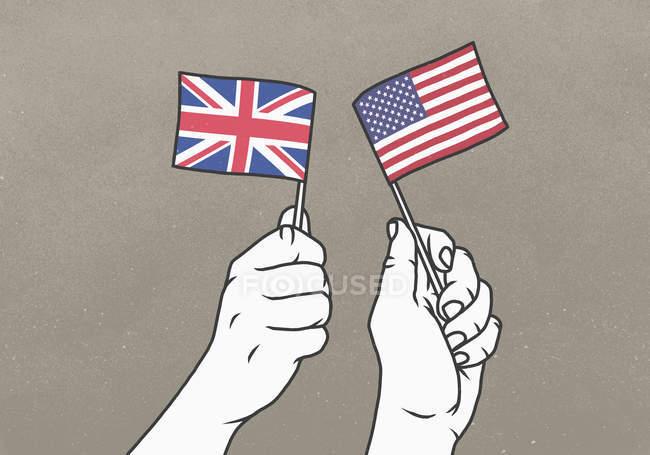 Los hombres que enarbolan pequeñas banderas británicas y estadounidenses - foto de stock