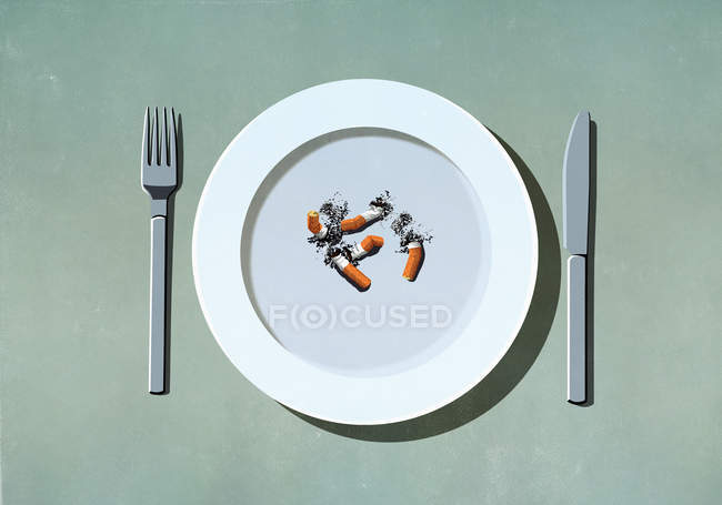 Cigarette butts on plate — Stock Photo