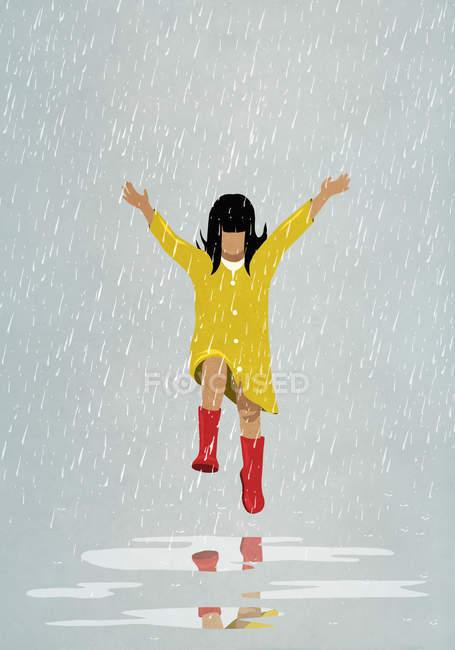 Chica despreocupada saltando en charcos de lluvia - foto de stock
