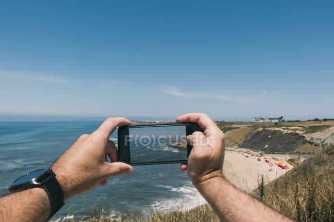 Perspectiva pessoal do homem com telefone da câmera fotografando ensolarado, oceano cênico — Fotografia de Stock