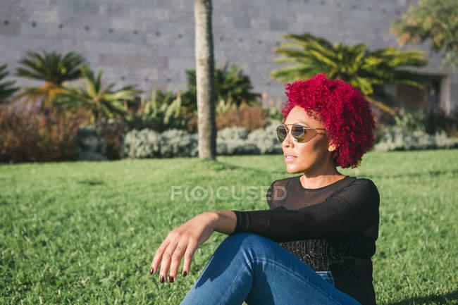 Donna con i capelli rossi rilassante nel parco soleggiato — Foto stock