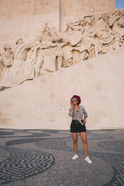 Elegante donna in occhiali da sole sotto Monument to the Discoveries, Lisbona, Portogallo — Foto stock