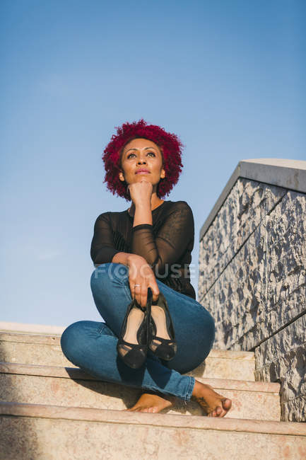 Жінка відпочиває на сонячних сходах. — стокове фото