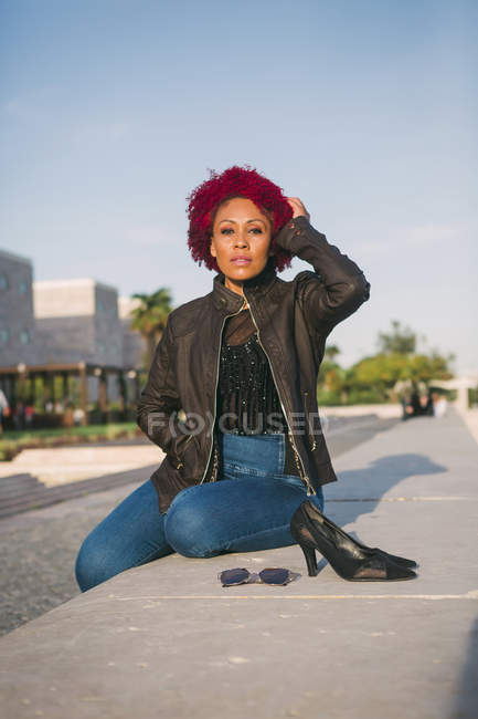 Portrait of confident, stylish woman relaxing in urban park — Stock Photo