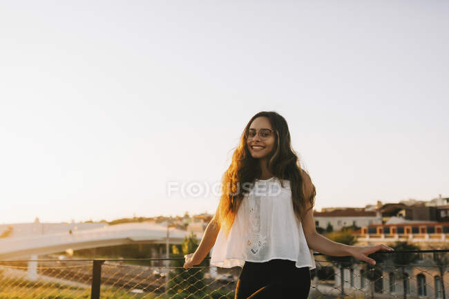 Ritratto di giovane donna sorridente nel soleggiato parco cittadino — Foto stock