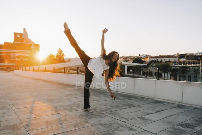Jeune danseuse ludique faisant se divise debout dans le parc ensoleillé de la ville — Photo de stock