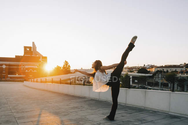Graceful young female dancer doing standing splits in sunny urban park — Stock Photo