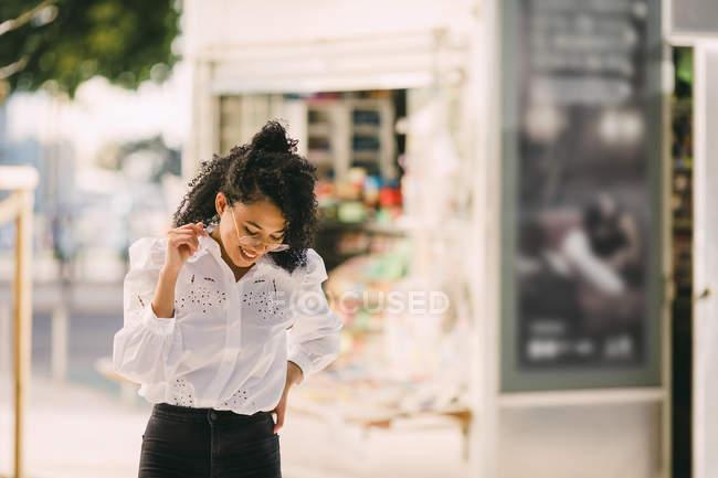 Bonne jeune femme marchant sur le trottoir urbain — Photo de stock