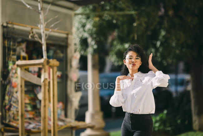 Portrait of playful young woman gesturing in sunny park — Stock Photo