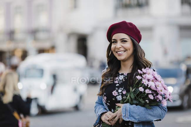 Portrait de jeune femme heureuse en béret avec bouquet de fleurs dans la rue urbaine — Photo de stock