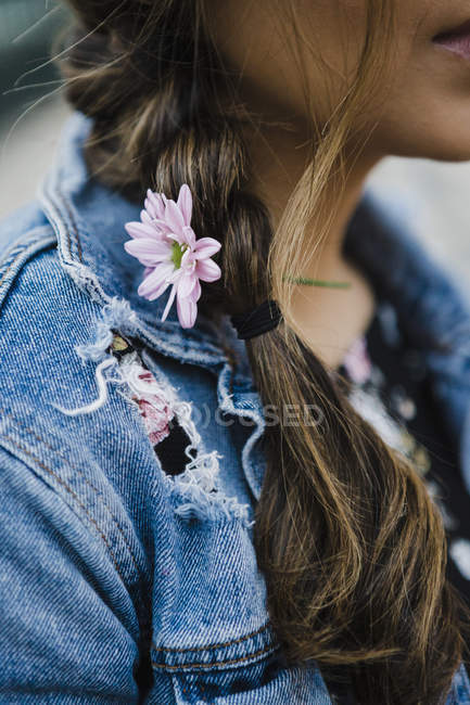 Close up of young woman with purple flower in braided hair — Stock Photo