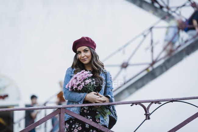 Portrait de femme en béret tenant bouquet de fleurs — Photo de stock