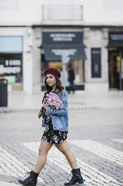 Портрет уверенной молодой женщины, переходящей улицу с букетом цветов — стоковое фото