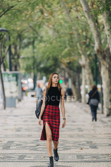 Затишна молода жінка, що ходить по міському парку. — стокове фото