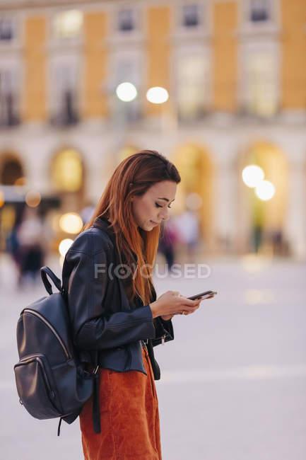 Молодая женщина с рюкзаком с помощью смартфона на городской тротуаре — стоковое фото