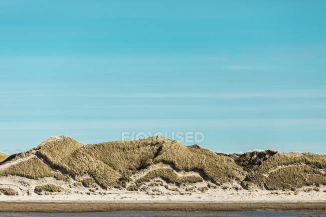 Спокойные песчаные дюны под солнечным голубым небом, Норддорф, Шлезвиг-Гольштейн, Германия — стоковое фото