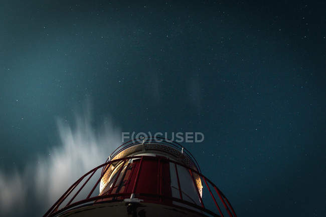 View from below lighthouse under starry night sky — стокове фото