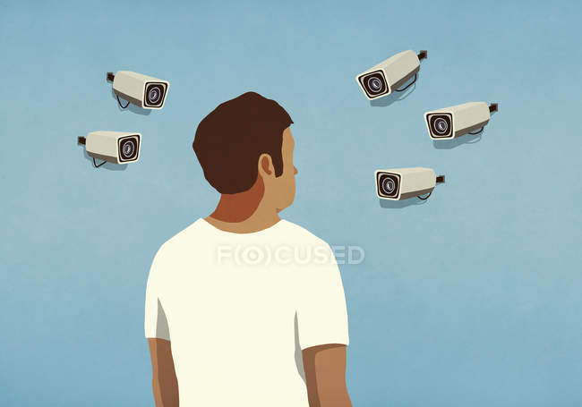 Surveillance cameras pointed at man — Stock Photo