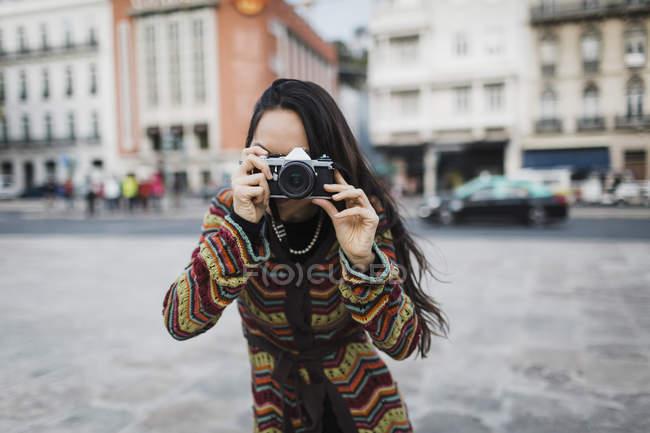 Портрет туристки с помощью камеры на городской улице — стоковое фото
