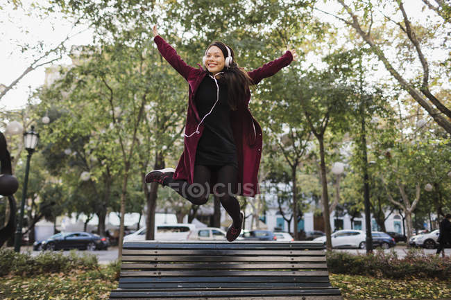 Portrait of playful exuberant woman jumping off urban city bench — Stock Photo