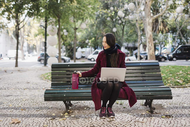 Woman with water bottle working at laptop in autumn city park — Stock Photo