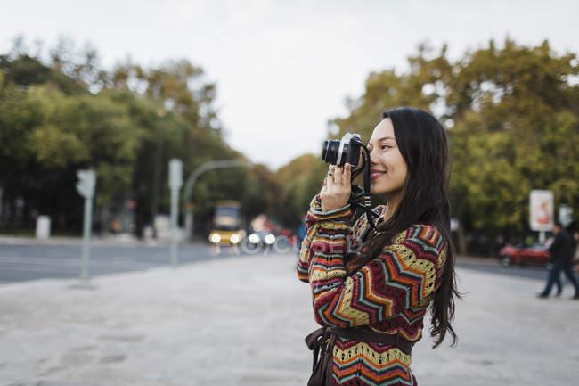 Turista feminino usando câmera na rua da cidade — Fotografia de Stock