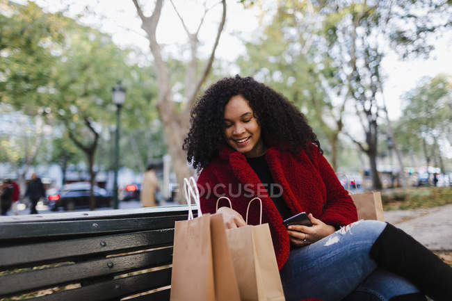 Smiling young woman looking in shopping bags on park bench — Stock Photo