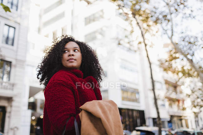 Young woman looking over shoulder on urban street — Stock Photo