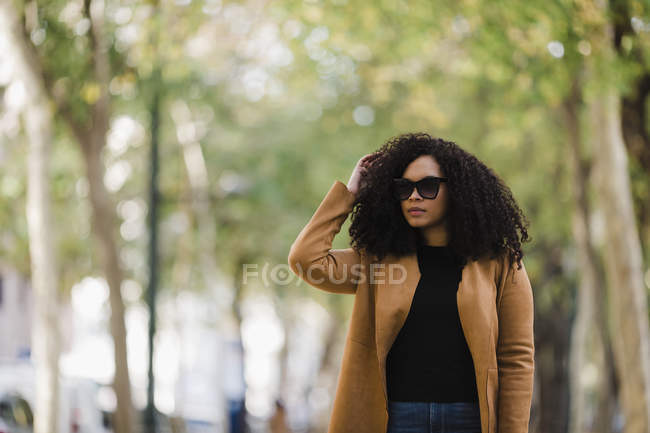 Stylish young woman in sunglasses walking in park — Stock Photo