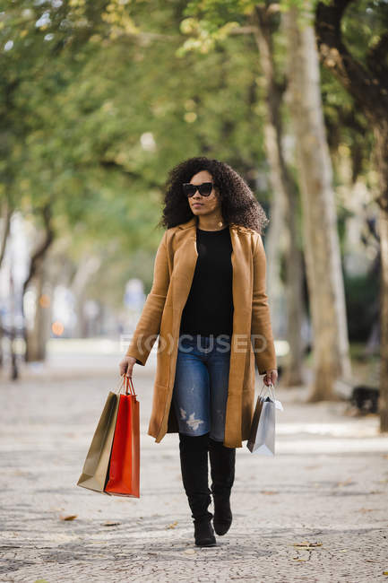 Stylish young woman walking with shopping bags on sidewalk — Stock Photo
