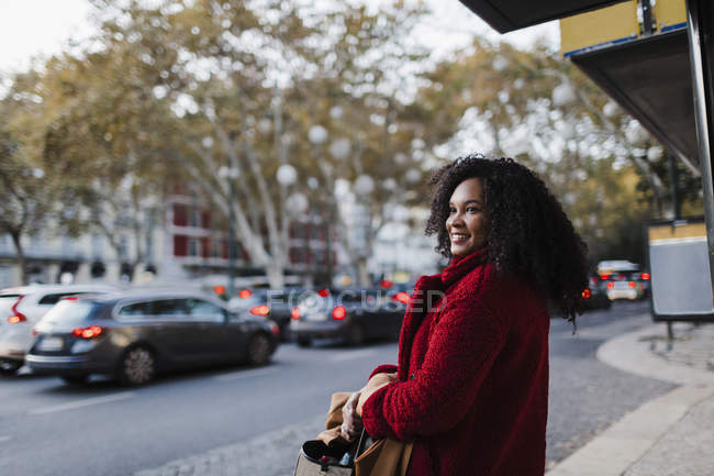 Smiling young woman on urban sidewalk — Photo de stock