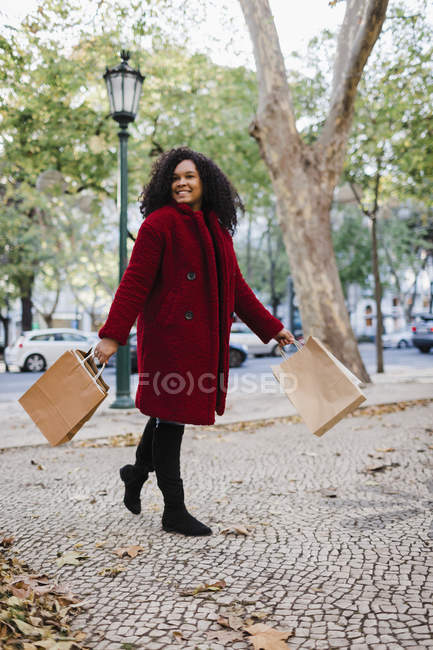 Portrait of carefree young woman walking with shopping bags in urban autumn park — Stock Photo