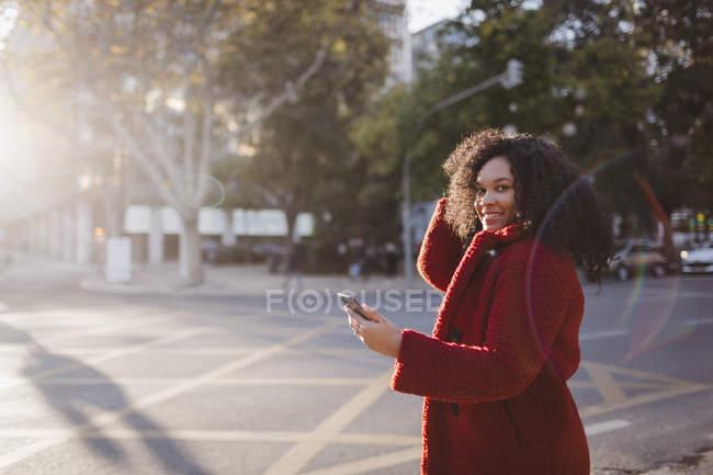 Retrato de mujer joven confiada y sonriente con teléfono inteligente en la calle soleada de la ciudad - foto de stock