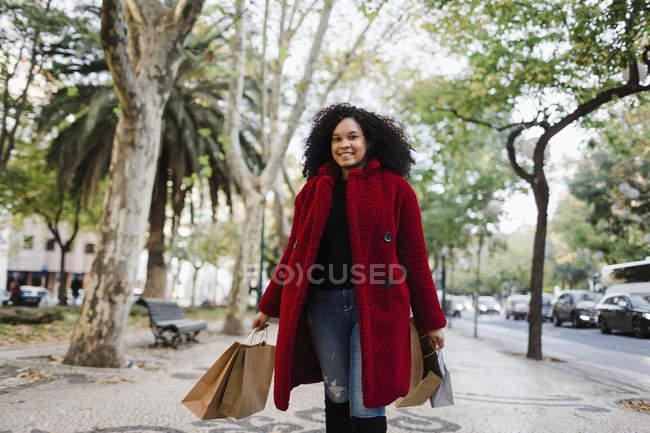 Портрет безтурботної молодої жінки з мішками для покупок. — стокове фото