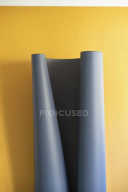 Graues Blatt, das sich auf gelbem Hintergrund entfaltet — Stockfoto