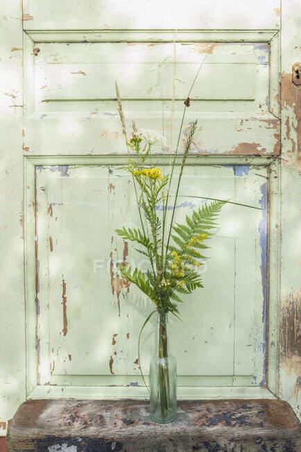 Tiges de fleurs jaunes et vertes dans un vase par porte avec peinture écaillée — Photo de stock