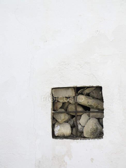 Quadratische Öffnung in Mauer mit gestapelten Steinen — Stockfoto